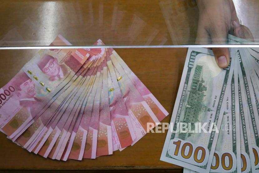 Petugas menunjukkan uang pecahan rupiah dan dolar AS (USD).