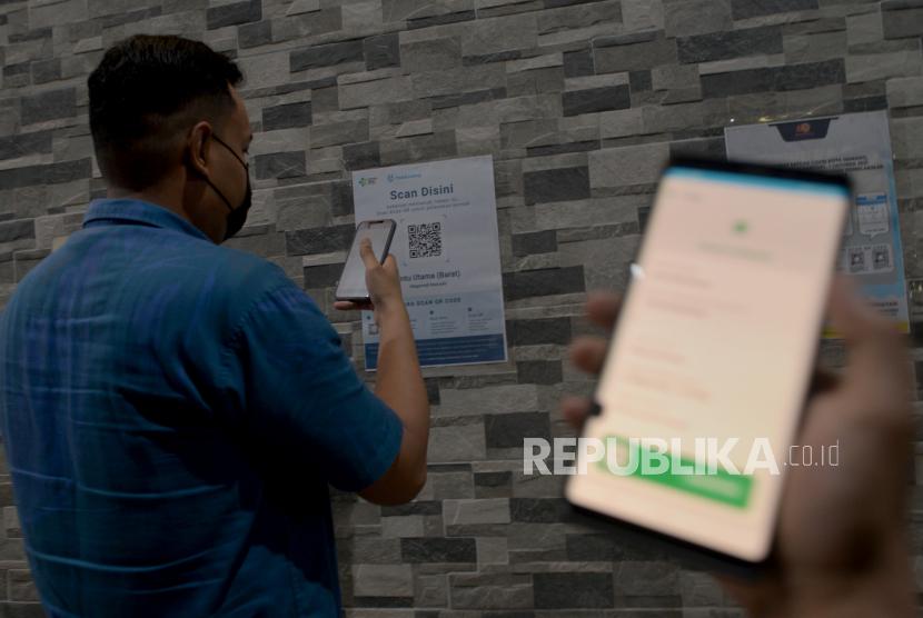 Pengunjung memindai kode batang (QR code) aplikasi PeduliLindungi sebelum memasuki pusat perbelanjaan. Mulai 1 Oktober 2021, pemberlakuan syarat wajib sertifikat atau kartu vaksinasi serta penerapan aplikasi PeduliLindungi diterapkan di sejumlah pusat perbelanjaan untuk mendukung pencegahan penyebaran Covid-19.