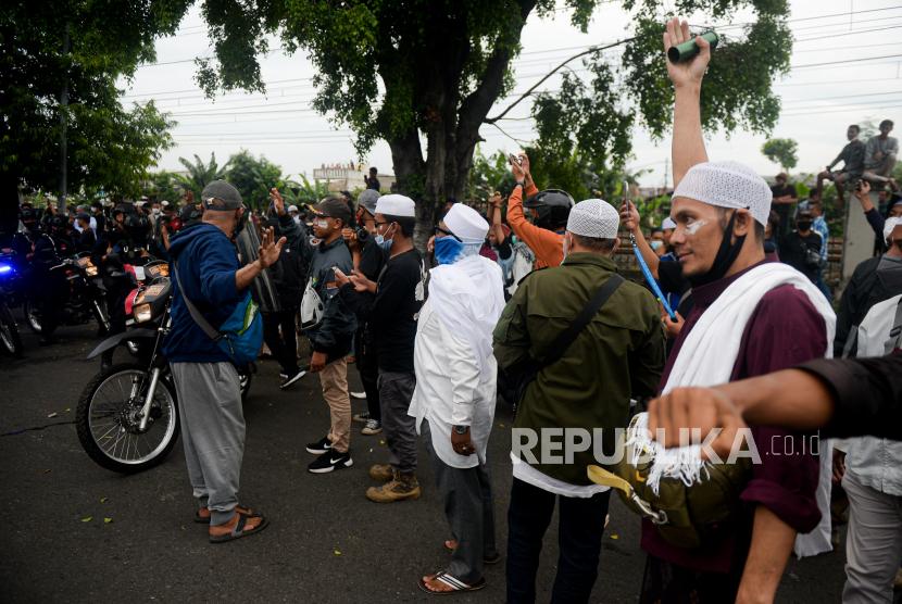 Massa aksi dari pendukung Habib Rizieq Shihab (HRS) memaksa memutar balik petugas Kepolisian saat berjaga di Jalan I Gusti Ngurah Rai menuju PN Jakarta Timur, Jakarta, Kamis (24/6). Aksi massa tersebut dalam rangka mengawal sidang pembacaan vonis terhadap Habib Rizieq Shihab terkait kasus tes Swab di Rumah Sakit Ummi, Bogor. Republika/Thoudy Badai