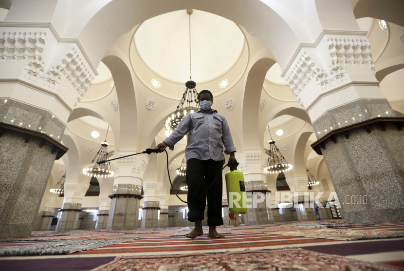Seorang petugas menyemprotkan disinfektan di masjid Al-Jaffali, Jeddah, Arab Saudi.