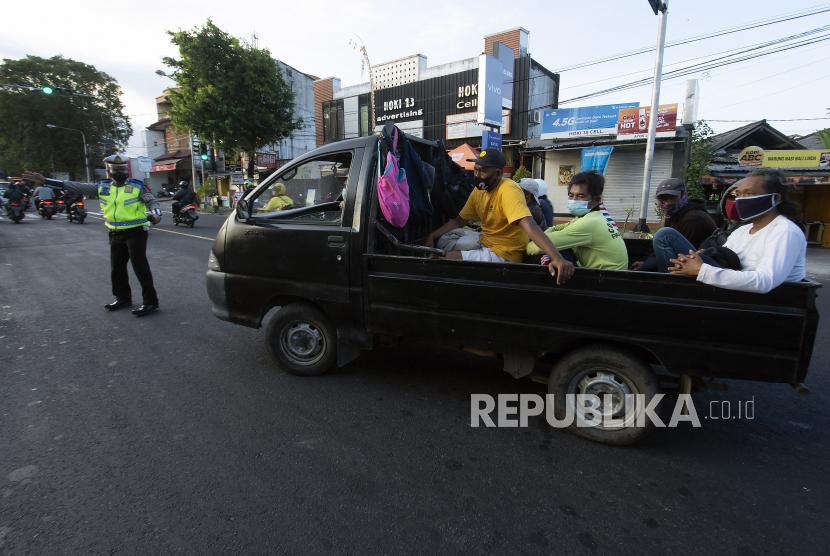 Personel Satlantas Polresta Denpasar menghentikan mobil bak terbuka berisi warga yang hendak berwisata (ilustrasi)