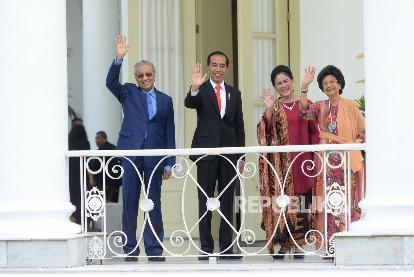 President Joko Widodo (second left) and Malaysian Prime Minister Mahathir Mohamad (left) accompanied by First Lady Iriana (second right) and Mahathir's wife DR Siti Hasanah (right) greet the reporters at Bogor Palace, West Java, Friday (June 29).