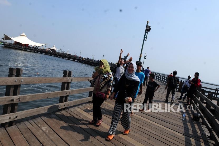 Sejumlah wisatawan berjalan di Jembatan Pantai Ancol, Jakarta, Ahad (17/6).