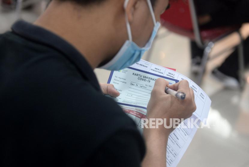 Seorang karyawan retail mengisi kartu vaksinasi Covid-19 saat vaksinasi massal di Mall BTM, Bogor, Jawa Barat, beberapa waktu lalu.
