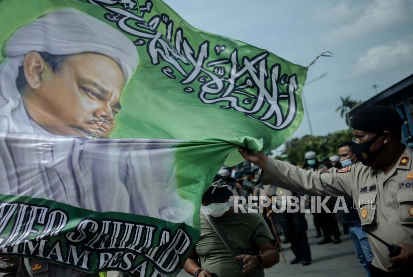 Aparat menyita banner Habib Rizieq Shihab saat  unjuk rasa 1812 Front Pembela Islam (FPI) di sekitar Patung Kuda Arjuna Wiwaha, Jakarta Pusat, Jumat (18/12).