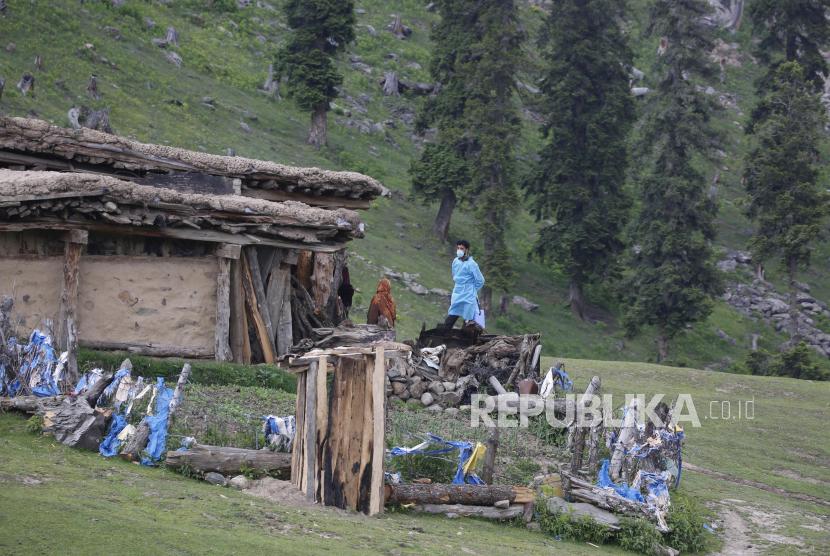 Petugas kesehatan membujuk keluarga gembala untuk disuntik vaksin Covid-19 di Tosa Maidan, distrik Budgam Kashmir tengah, India, Senin (21/6). Lokasi yang jauh sekitar 52 kilometer dari Srinagar, India, membuat para tenaga kesehatan harus berjalan melewati hamparan padang rumput dalam mengajak penduduk lokal sekitar untuk menjalani vaksinasi Covid-19. EPA-EFE/FAROOQ KHAN
