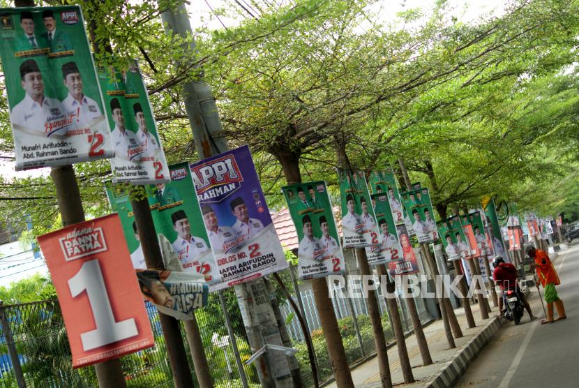 Petugas kebersihan menyapi di dekat alat peraga kampanye (APK) yang terpasang di pohon dan tiang listrik di Makassar, Sulawesi Selatan, Rabu (14/10/2020). Pemasangan sejumlah APK tersebut melanggar aturan Komisi Pemilihan Umum (KPU) Kota Makassar melalui surat keputusan (SK) nomor 340/PL.02.4-kpt/7371/KPU-kot/IX/2020 tentang pemasangan APK pada Pilkada 2020.