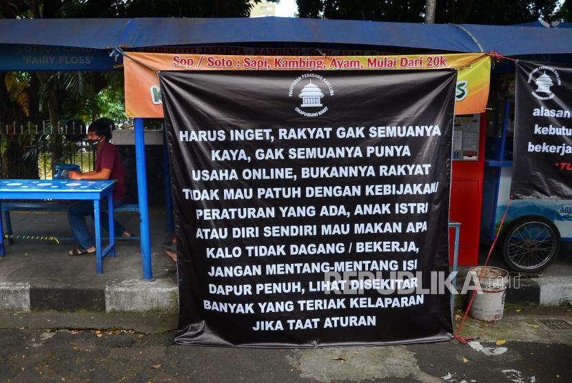 Sejumlah spanduk dipasang oleh Paguyuban Pedagang Kaki Lima terkait dampak PPKM yang dirasakan para pedagang kaki lima (PKL) di Jalan Cikapundung Barat, Kota Bandung, Jumat (16/7). Spaduk tersebut berisi harapan kepada pemerintah agar ada kebijakan dan solusi untuk mengatasi masalah yang dihadapi para pedagang kecil seperti PKL di saat penerapan PPKM Darurat.