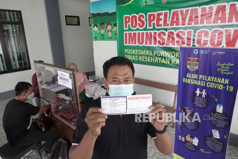 Seorang wartawan menunjukan kartu vaksinasi COVID-19  tahap pertama, di Pukesmas Purwokerto Barat, Banyumas, Jateng, Kamis (25/2/2021). Sejumlah wartawan di Kabupaten Banyumas, Jateng, mengikuti vaksinasi COVID-19 tahap dua termin pertama yang ditujukan bagi kelompok pelayanan publik seperti Polri, Aparatur Sipil Negara, Satpol PP,  dan Wartawan.