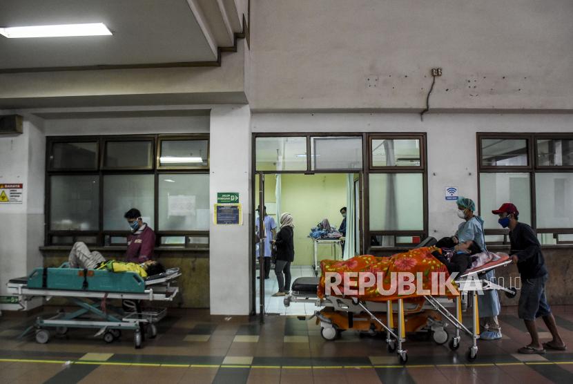 Keluarga pasien bersama petugas kesehatan membawa pasien ke ruang Instalasi Gawat Darurat (IGD) Rumah Sakit Dokter Hasan Sadikin (RSHS), Kota Bandung, Ahad (13/6). Berdasarkan data dari Pusat Informasi dan Koordinasi Covid-19 Provinsi Jawa Barat (Pikobar) pada (12/6), tingkat keterisian tempat tidur atau Bed Occupancy Rate (BOR) rumah sakit yang melayani Covid-19 dan tidak melayani Covid-19 telah mencapai 67,31 persen dengan rincian sebanyak 9.120 dari total 13.550 tempat tidur telah terisi. Foto: Republika/Abdan Syakura