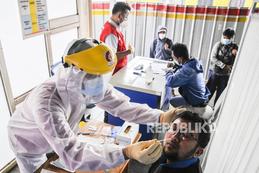 Petugas medis (kiri) melakukan tes usap antigen kepada calon penumpang KRL (Kereta Rel Listrik) di Stasiun Bekasi, Jawa Barat, Senin (21/6/2021). PT KAI Commuter melakukan tes acak kepada penumpang KRL dari tanggal 21-27 Juni 2021 guna mencegah penyebaran wabah COVID-19.