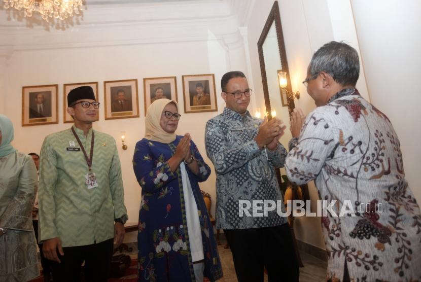 Gubernur DKI Jakarta Anies Baswedan ( kanan) didampingi istrinya dan Wakil Gubernur Sandiaga Uno (kiri) bersalaman dengan pegawai Pemprov DKI Jakarta saat halal bihalal, di Balaikota, Jakarta, Kamis (21/6).