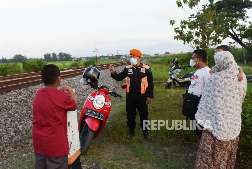 Seorang Polisi Khusus Kereta Api (Polsuska) memberikan sosialisasi pada warga di sekitar jalur Kereta Api (KA) saat melakukan pengawasan dan pengamanan jalur di Kota Madiun, Jawa Timur, Senin (19/4/2021). Kegiatan tersebut sebagai antisipasi agar aktivitas warga di jalur KA tidak membahayakan perjalanan KA, karena beberapa kali ditemukan keisengan warga menaruh batu di atas rel.
