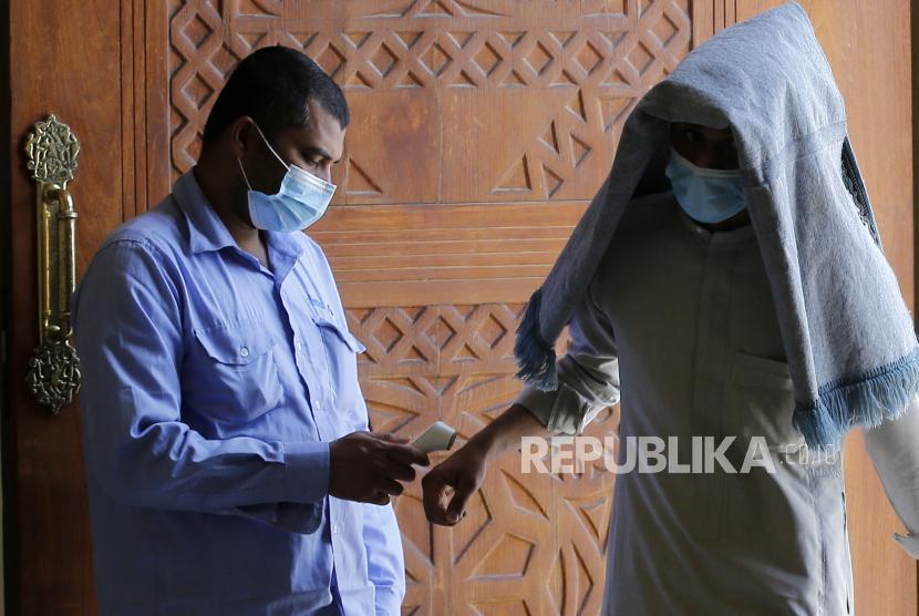 Arab Saudi Lakukan Lebih dari 28 Juta Tes Covid-19. Seorang petugas mengukur suhu tubuh jamaah sebelum melaksanakan Shalat Jumat di masjid Al-Jaffali, Jeddah, Arab Saudi, Jumat (30/4). Selama Ramadhan 1442 Hijriah ini umat Muslim bisa menyelenggarakan Shalat berjamaah di Masjid dengan mematuhi protokol kesehatan seperti mengenakan masker dan menjaga jarak sosial untuk menghindari penyebaran virus Covid-19.  (AP Photo/Amr Nabil)