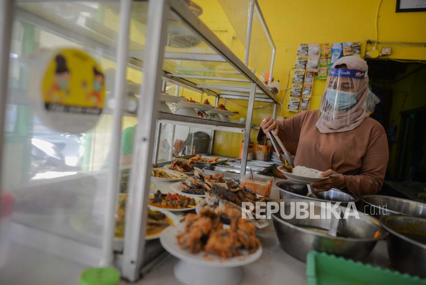Pemilik warteg melayani warga yang hendak makan di Warteg yang menerapkan protokol kesehatan di kawasan Cilandak Timur, Jakarta Selatan, Ahad (19/7). Pemerintah menyalurkan pinjaman kredit modal kerja sebesar Rp 4,2 Triliun untuk satu juta pelaku usaha mikro, kecil, dan menengah (UMKM) dalam rangka mempercepat pemulihan ekonomi nasional akibat dampak pandemi covid-19.