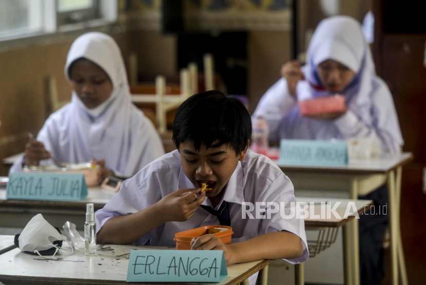 PTM wajib dihentikan jika ada kasus Covid-19/Sejumlah pelajar menyantap hidangan bekal yang dibawanya disela pelaksanaan Pembelajaran Tatap Muka Terbatas (PTMT) di SMP Negeri 1 Kota Bogor, Jawa Barat, Senin (4/10). Sebanyak 200 sekolah tingkat SMP dan SMA di Kota Bogor melaksanakan PTMT dengan menerapkan protokol kesehatan yang ketat dan peserta didik sudah mendapatkan vaksin dosis kedua.  Republika/Putra M. Akbar