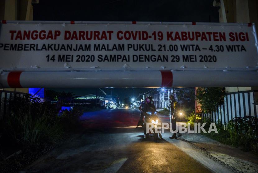 Petugas kepolisian memberi pemahaman kepada pengendara yang mencoba melewati portal pintu masuk ke wilayah Kabupaten Sigi di Desa Baliase, Sigi, Sulawesi Tengah, Kamis (14/5/2020) malam. Pemerintah Kabupaten Sigi memberlakukan jam malam mulai 14 - 29 Mei 2020 antara pukul 21