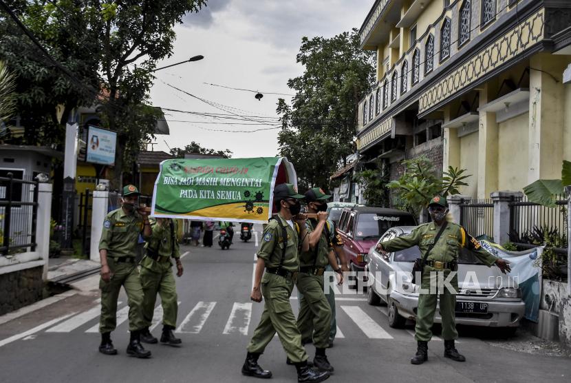 Petugas Linmas memanggul replika keranda mayat saat sosialisasi perpanjangan Pemberlakuan Pembatasan Kegiatan Masyarakat (PPKM) Skala Mikro di Cimahi Tengah, Kota Cimahi, Selasa (23/2). Pemerintah memperpanjang Pemberlakuan Pembatasan Kegiatan Masyarakat (PPKM) Skala Mikro di Jawa dan Bali meliputi 123 kabupaten/kota di tujuh provinsi yakni DKI Jakarta, Banten, Jawa Barat, Jawa Tengah, Jawa Timur, DI Yogyakarta dan Bali mulai 23 Februari hingga 8 Maret guna menekan laju kasus serta mencegah penyebaran Covid-19 di tingkat desa atau kelurahan. Foto: Abdan Syakura/Republika