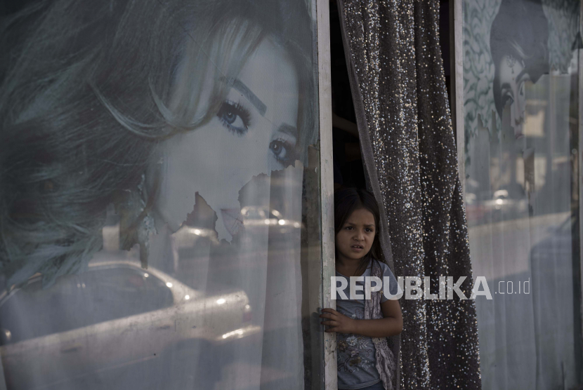 Taliban Perintahkan Siswa Laki-Laki Kembali ke Sekolah. Seorang gadis Afghanistan melihat keluar dari sebuah salon kecantikan di Kabul, Afghanistan, Kamis, 16 September 2021. Sejak Taliban menguasai Kabul, beberapa gambar yang menggambarkan wanita di luar salon kecantikan telah dihapus atau ditutup-tutupi.