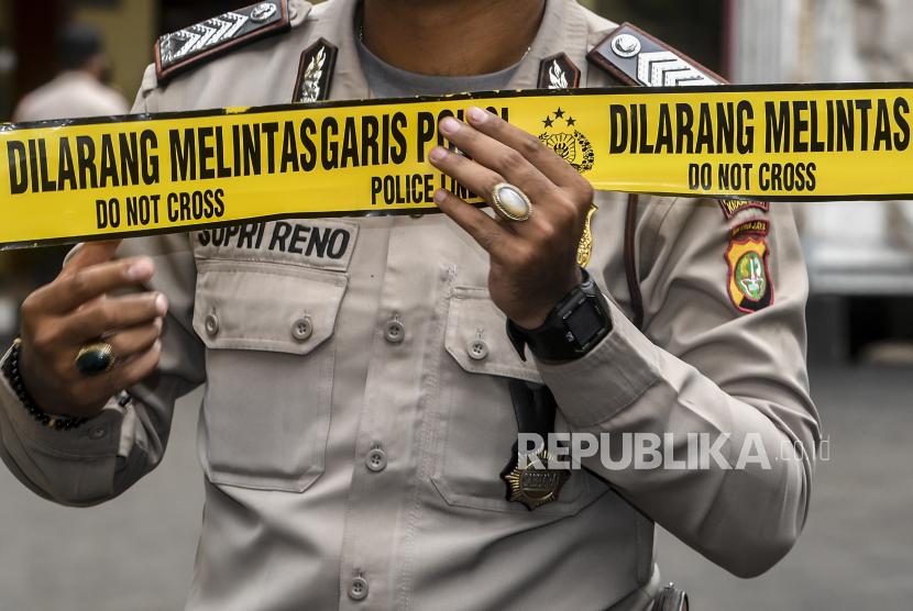 Petugas kepolisian memasang batas garis polisi (ilustrasi).