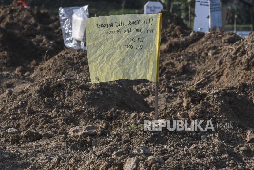 Bendera kuning sebagai pengganti nisan berada di pusara kasus meninggal akibat Covid-19. (ilustrasi)