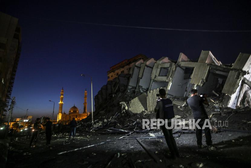 Warga Palestina memeriksa menara Hanadi yang hancur di Kota Gaza, 11 Mei 2021. Setidaknya satu wanita tewas setelah 130 roket yang ditembakkan oleh Hamas dari Jalur Gaza jatuh di Tel Aviv dan kota-kota tetangga Israel.