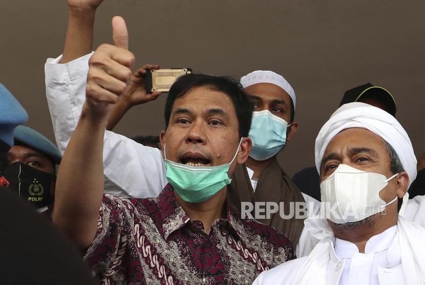 FILE - Pada file foto Sabtu 12 Desember 2020 ini, Sekretaris Jenderal Front Pembela Islam Munarman, kiri, yang juga pengacara ulama Rizieq Shihab (kanan) memberi isyarat kepada wartawan setelah Rizieq diinterogasi di Polda Kantor pusat di Jakarta, Indonesia. Anggota pasukan polisi kontraterorisme Indonesia pada Selasa, 27 April 2021.