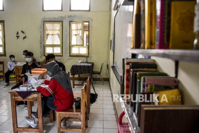 Vaksinator menyuntikkan vaksin Covid-19 ke pelajar di SMPN 7 Bandung, Jalan Ambon, Kota Bandung, Selasa (21/9). Pemerintah Kota Bandung menyatakan program vaksinasi Covid-19 dosis pertama bagi pelajar di Kota Bandung telah mencapai 76 persen dan dosis kedua mencapai 50 persen. Foto: Republika/Abdan Syakura
