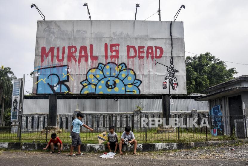 Sejumlah anak bermain di dekat mural yang bertuliskan Mural Is Dead di kawasan Monumen Perjuangan Rakyat Jawa Barat, Kota Bandung, Jumat (27/8). Mural tersebut merupakan bentuk ekspresi dari sejumlah seniman sekaligus media penyampaian kritik sosial kepada pemerintah di masa pandemi Covid-19. Foto: Republika/Abdan Syakura