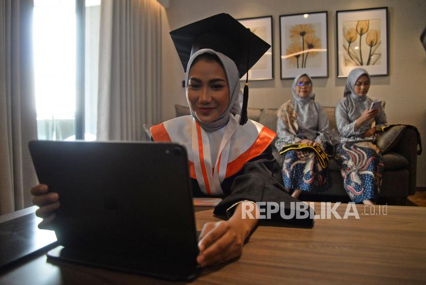 Wisudawati Annisa Bunga Fitri didampingi keluarganya mengikuti wisuda secara online Universitas Sahid di Jakarta, Sabtu (25/9). Universitas sahid menggelar wisuda ditengah pandemi Covid-19 secara hybrid yaitu offline dengan protokol kesehatan yang ketat dan secara online melalui aplikasi zoom & youtube yang diikuti oleh 454 wisudawan/wisudawati.
