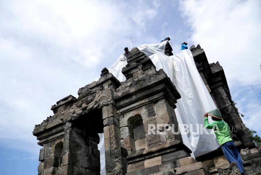 Petugas BPCB Jawa Tengah menutup bagian utama Candi Ngawen dengan plastik UV di Muntilan, Jawa Tengah, Kamis (4/2). Balai Pelestarian Cagar Budaya (BPCB) Jawa Tengah menutup permukaan Candi Ngawen dengan plastik untuk mengantisipasi abu vulkanik dari Erupsi Gunung Merapi. Penutupan permukaan Candi ini setelah Candi Borobudur dan Candi Mendut.