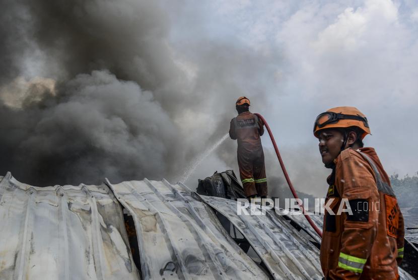 Petugas Pemadam Kebakaran berusaha memadamkan api yang melalap gudang alat pesta di kawasan Cinangka, Depok, Jawa Barat, Senin (2/8). Sebanyak 15 pemadam kebakaran memadamkan api yang melalap gudang berisi alat pesta event organizer yang hingga saat ini penyebab kebakaran masih berlangsung dan kerugian belum diketahui.