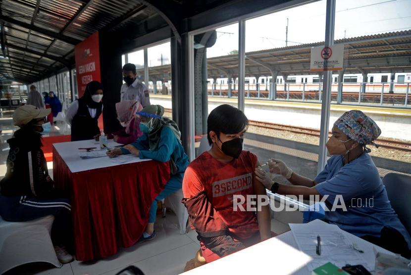 Tenaga kesehatan menyuntikkan vaksin COVID-19 kepada warga di stasiun kereta api.