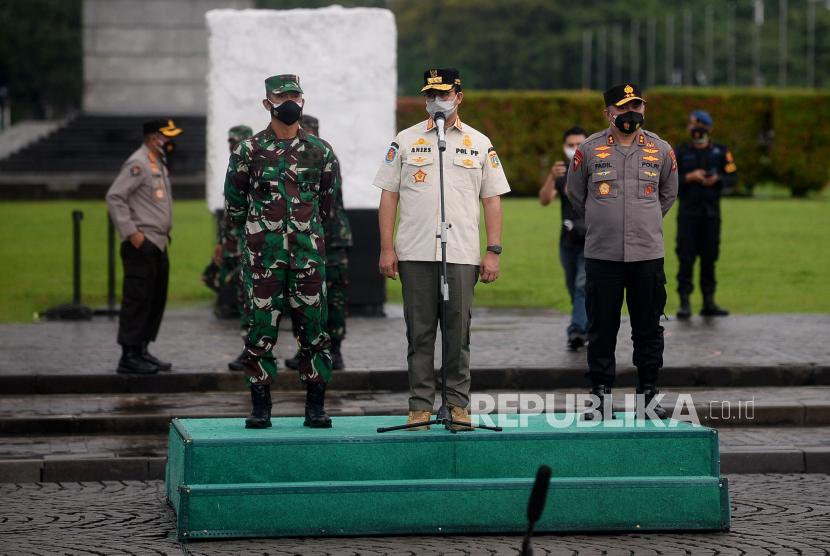 Gubernur DKI Jakarta Anies Baswedan memberikan arahan saat gelar pasukan dalam rangka pengetatan PPKM Mikro di wilayah DKI Jakarta di Lapangan Monas, Jakarta, Jumat (18/6). Gelar pasukan dalam rangka pengetatan PPKM Mikro yang diikuti oleh personel gabungan dari TNI, Polri dan Satpol PP tersebut sebagai upaya menekan penyebaran Covid-19 di DKI Jakarta yang terus meningkat beberapa hari belakangan ini.Prayogi/Republika
