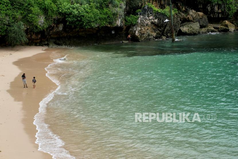 Wisatawan menikmati pasir putih di Pantai Gesing, Panggang, Gunungkidul, Yogyakarta.