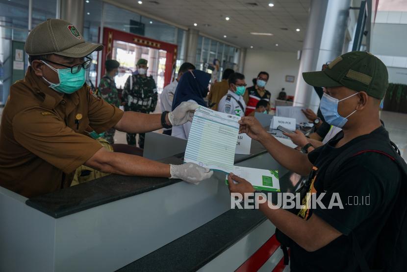 Petugas mengecek surat keterangan hasil negatif tes PCR penumpang pesawat  (ilustrasi)
