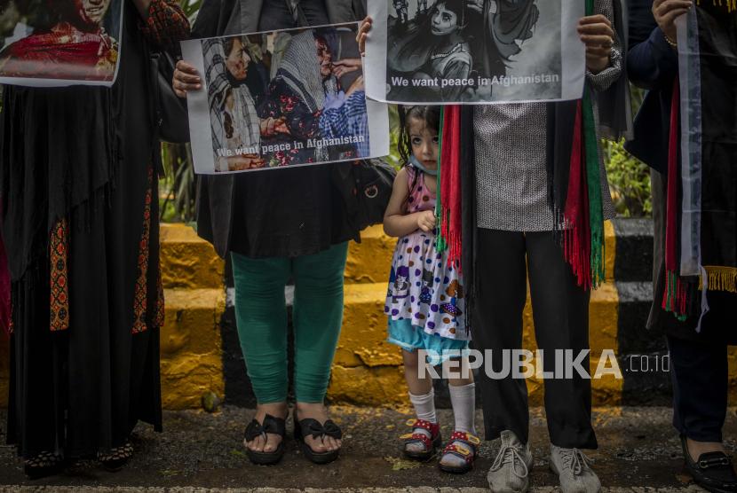 Seorang gadis muda Afghanistan berdiri di samping ibunya berpartisipasi dengan wanita Afghanistan lainnya melawan Pakistan dan pengambilalihan Taliban di Afghanistan, di New Delhi, India, Kamis, 16 September 2021.
