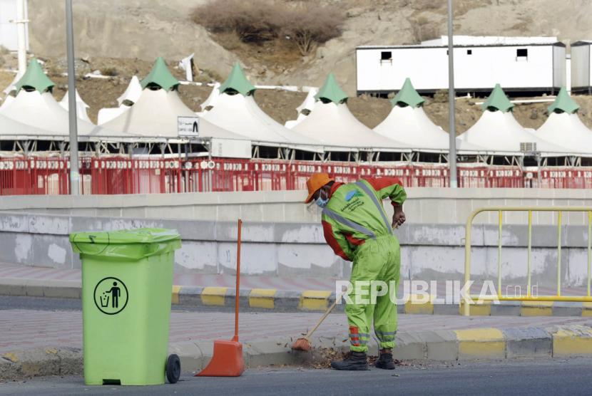 Seorang pekerja membersihkan jalan menjelang pelaksanaan ibadah haji tahunan di dekat tenda kemah di Mina,Selasa (13/7). Untuk 2 tahun berturut-turut pelaksanaan ibadah haji di batasi karena pandemi covid-19.