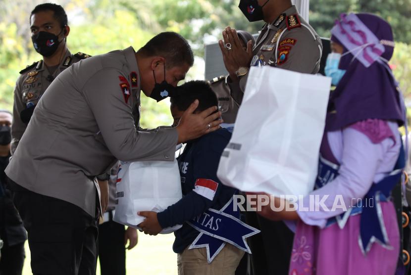 Wakapolda Jawa Timur Brigjen Pol Slamet Hadi Supraptoyo (kiri) mencium kening seorang anak asuh saat peringatan Hari Lalulintas Bhayangkara di Tugu Pahlawan, Surabaya, Jawa Timur, Jumat (17/9/2021). Direktorat Lalu lintas (Ditlantas) Polda Jawa Timur menggelar berbagai kegiatan untuk menyambut Hari Lalulintas Bhayangkara salah satunya dengan mengadakan program pengangkatan orang tua asuh bagi anak yatim piatu terdampak COVID-19 bernama Satu Polantas Satu Anak Yatim Piatu.