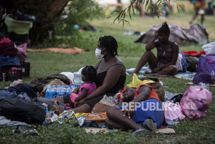 Migran Haiti beristirahat di sebuah perkemahan di sebuah taman olahraga di Ciudad Acua, Meksiko, Selasa, 21 September 2021. Pihak berwenang AS telah bergerak untuk mengusir banyak migran yang berkemah di sekitar jembatan di Del Rio, Texas, setelah menyeberang dari Ciudad Acuna, Meksiko. Para pejabat juga berusaha menghalangi orang lain melintasi perbatasan dari Meksiko.