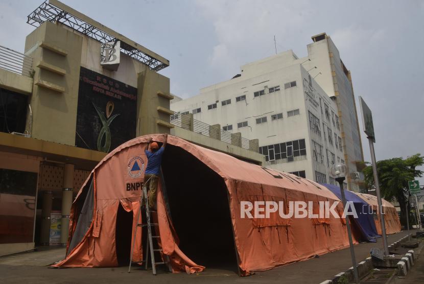 Seorang petugas membongkar tenda darurat yang dijadikan ruang triase di halaman RSUD Bekasi, Jawa Barat, Selasa (3/8/2021). Pemerintah setempat membongkar tenda darurat karena penurunan pasien positif COVID-19 dan penambahan ruang perawatan di Rumah Sakit Darurat (RSD) Stadion Patriot Chandrabhaga yang dapat menampung 217 pasien bergejala ringan.