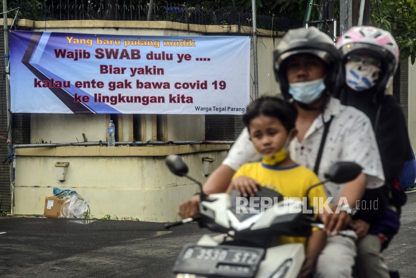 Pengendara melintas di dekat spanduk peringatan untuk pemudik di kawasan Tegal Parang, Jakarta, Senin (17/5). Spanduk tersebut untuk memperingati warga yang kembali dari kampung halaman agar membawa surat bebas COVID-19. Republika/Putra M. Akbar