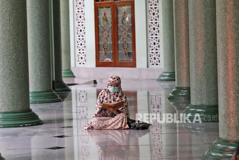 Seorang perempuan yang memakai masker sebagai antisipasi wabah virus Corona membaca kitab suci Alquran sambil menunggu waktu berbuka puasa di hari pertama Ramadhan, di sebuah masjid di Jakarta, Indonesia, Selasa, 13 April 2021