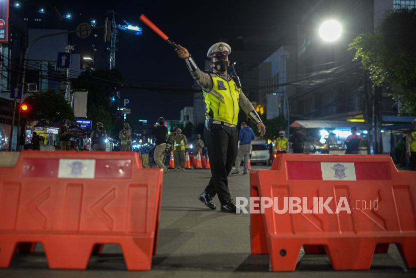 Petugas kepolisian mengatur lalu lintas saat penutupan akses jalandalam rangka pembatasan kegiatan masyarakat mengingat kasus positif Covid-19 harian.
