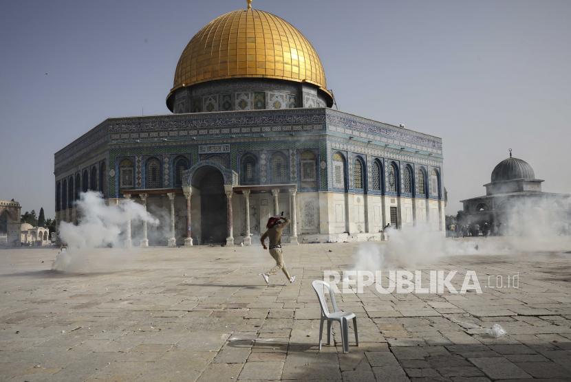 Pria Palestina melarikan diri dari gas air mata saat bentrokan dengan pasukan keamanan Israel di depan Masjid Kubah Batu di kompleks Masjid Al Aqsa di Kota Tua Yerusalem Senin (10/5).