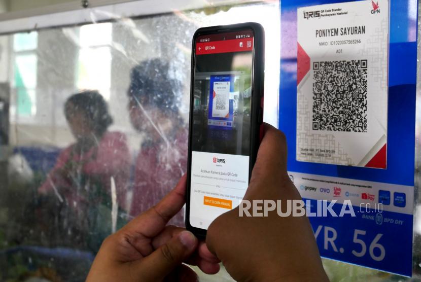 Pembeli bertransaksi dengan metode pemindaian QRIS dengan aplikasi DOKU e-Wallet di Pasar Tradisional Prawirotaman, Yogyakarta, Ahad (6/9).  Saat ini Pemerintah Kota Yogyakarta mulai mengenalkan transaksi nontunai di pasar tradisional. Sebagai percontohan diterapkan di Pasar Beringharjo dan Pasar Prawirotaman. DOKU e-Wallet salah satu aplikasi yang bisa digunakan untuk bertransaksi dengan QRIS antarplatform.