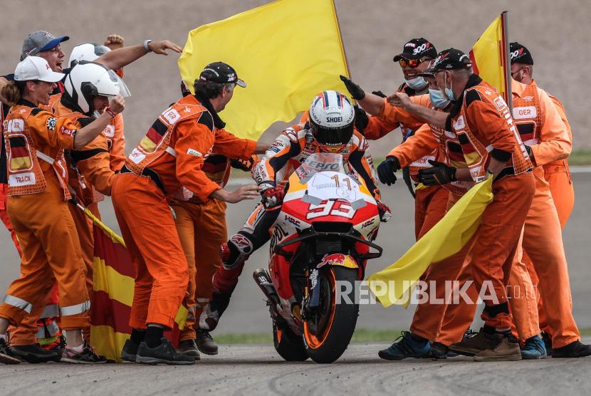 Pembalap MotoGP Spanyol Marc Marquez (tengah) dari Tim Repsol Honda merayakan kemenangannya bersama para track marshal setelah memenangkan Grand Prix Sepeda Motor Jerman di sirkuit balap Sachsenring di Hohenstein-Ernstthal, Jerman, 20 Juni 2021.