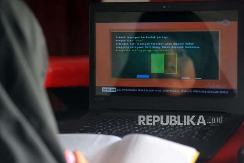 Seorang murid sekolah dasar (SD) belajar melalui siaran streaming TVRI di rumahnya.