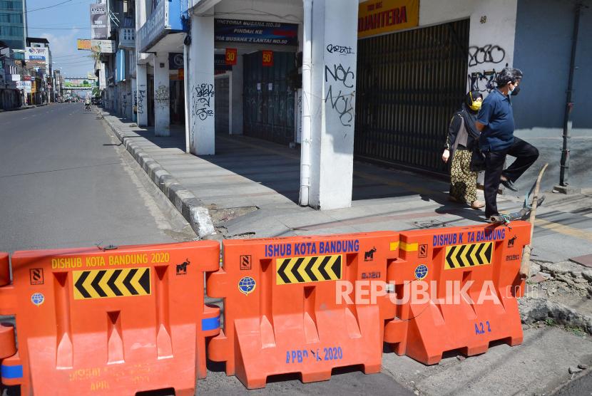 Suasana lengang di salah satu tempat yang biasa dipadati pengunjung di pusat Kota Bandung yaitu kawasan Pasar Baru, saat penutupan sementara di masa Pemberlakuan Pembatasan Kegiatan Masyarakat (PPKM) Darurat, Selasa (6/7). Penutupan sejumlah ruas jalan dan aktivitas perdagangan di pusat Kota Bandung, dalam rangka PPKM Darurat sebagai upaya mencegah penyebaran Covid-19.