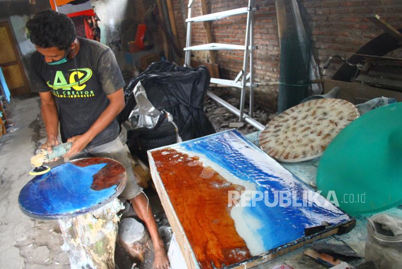 Perajin mebel membuat meja hias dari limbah kayu dan resin di Mangliawan, Malang, Jawa Timur, Jumat (25/6/2021). Perajin mebel setempat berupaya meningkatkan penjualan dengan memasarkan produknya melalui jejaring sosial serta berinovasi dengan teknik penggabungan limbah kayu dan resin guna meningkatkan nilai jual produknya. ANTARA FOTO/Ari Bowo Sucipto/wsj.